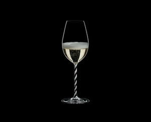 RIEDEL Fatto A Mano Champagne Wine Glass Black & White R.Q. filled with a drink on a black background