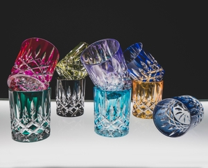 9 unfilled RIEDEL Laudon tumblers of different colors on an illuminated glass table.