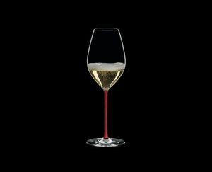 RIEDEL Fatto A Mano Champagne Wine Glass Red filled with a drink on a black background