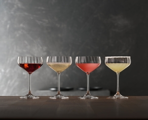 4 different cocktails stand side by side, served in SPIEGELAU Lifestyle Coupette glasses on a table in front of a grey wall.