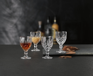 4 Nachtmann Noblesse Liqueur Goblets stand on a black counter. Three glasses are filled with spirits, 1 glass is empty. Blurred in the background stand 3 bottles of spirits.