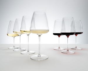 All seven glasses of the RIEDEL Winewings range stand on a grey ground. The red wine glasses are filled with red wine, the white wine glasses are filled with white wine and the Champagne glass is filled with Champagne.
