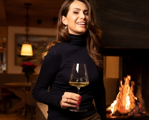 Brunette lady sits next to a fireplace in a living room and holds a filled RIEDEL Champagne Wine Glass in her hand.