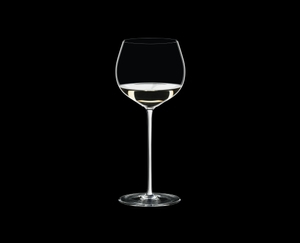 RIEDEL Fatto A Mano Oaked Chardonnay White filled with a drink on a black background