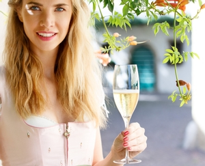 Woman in a traditional summer dress stands under a flowering shrub holding a filled RIEDEL Sommeliers Vintage Champagne Glass