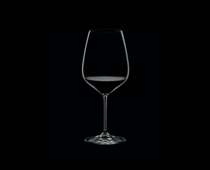RIEDEL Extreme Cabernet filled with a drink on a black background