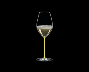 RIEDEL Fatto A Mano Champagne Wine Glass Yellow R.Q. filled with a drink on a black background