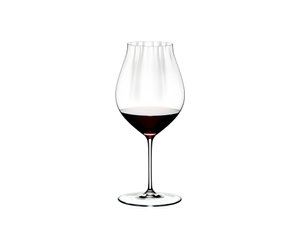 A woman holds a RIEDEL Performance Pinot Noir glass filled with red wine in one hand and a bottle of red wine in the other.