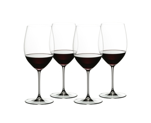 4 red wine filled RIEDEL Veritas Cabernet/Merlot glasses stand slightly offset next to each other on white background