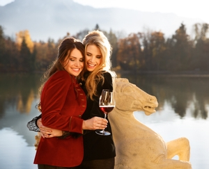 Two women hug in front of a lake in autumn, holding a red wine filled RIEDEL Sommeliers Bordeaux Grand Cru glass.