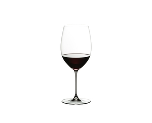 A woman sits on an armchair and looks at the red wine in the RIEDEL Veritas Cabernet/Merlot glass she holds in her hand.