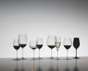 8 different RIEDEL Sommeliers glasses filled with red wine, white wine and sparkling wine stand on a grey ground