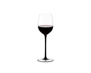 RIEDEL Sommeliers Black Tie Mature Bordeaux rempli avec une boisson sur fond blanc