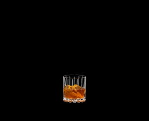 RIEDEL Drink Specific Glassware Neat filled with a drink on a black background