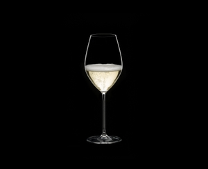 RIEDEL Veritas Restaurant Champagne Wine Glass filled with a drink on a black background