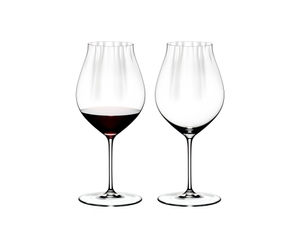Two RIEDEL Performance Pinot Noir glasses side by side. The glass on the left side is filled with red wine, the other one is empty.