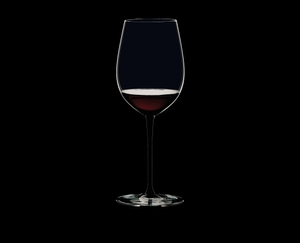 RIEDEL Sommeliers Black Tie Bordeaux Grand Cru filled with a drink on a black background