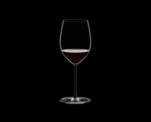 RIEDEL Fatto A Mano Cabernet/Merlot Black R.Q. filled with a drink on a black background