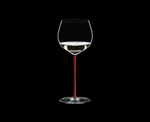RIEDEL Fatto A Mano Oaked Chardonnay Red filled with a drink on a black background