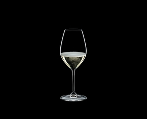 RIEDEL Restaurant Champagne Wine Glass filled with a drink on a black background