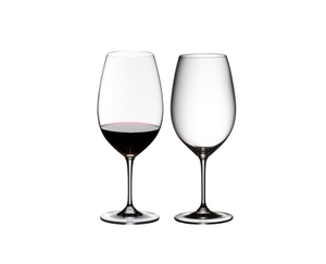 Two RIEDEL Vinum Syrah/Shiraz/Tempranillo glasses side by side. The glass on the left side is filled with red wine, the other one is empty.