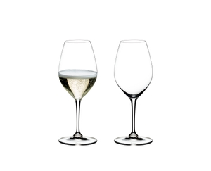 2 RIEDEL Vinum Champagne Wine Glasses standing side by side on white background. The glass on the left side is filled with Champagne, the other one is empty.