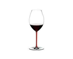 RIEDEL Fatto A Mano Syrah Red filled with a drink on a white background