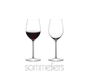 Two RIEDEL Sommeliers Mature Bordeaux/Chablis/Chardonnay glasses stand side by side on white background. The glass on the left side is filled with red wine, the other one is empty. Below the two glasses is the Sommeliers logo.