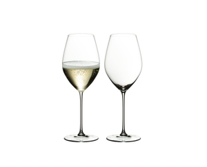 Two glasses RIEDEL Veritas Champagne Wine on a white background. The glass on the left side is filled with champagne, the other one is unfilled.