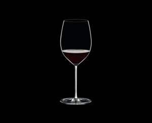RIEDEL Fatto A Mano Cabernet/Merlot White R.Q. filled with a drink on a black background
