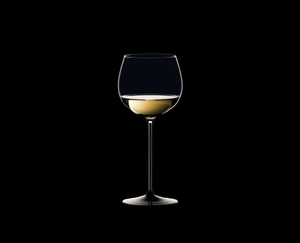RIEDEL Sommeliers Black Tie Montrachet filled with a drink on a black background
