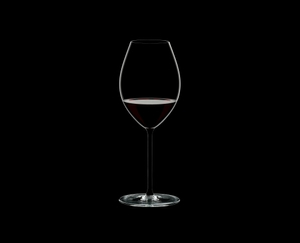 RIEDEL Fatto A Mano Syrah Black filled with a drink on a black background
