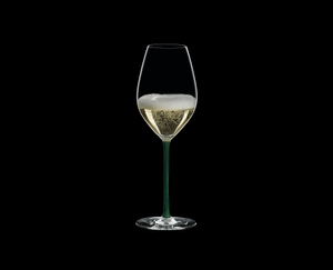RIEDEL Fatto A Mano Champagne Wine Glass Green filled with a drink on a black background
