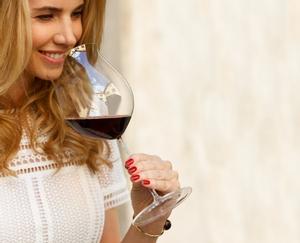 A RIEDEL Superleggero Burgundy Grand Cru glass filled with red wine on a white background.