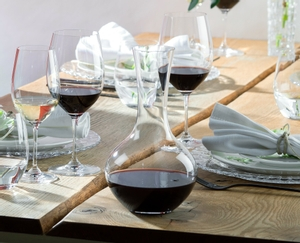Red wine filled RIEDEL Syrah Decanter on white background