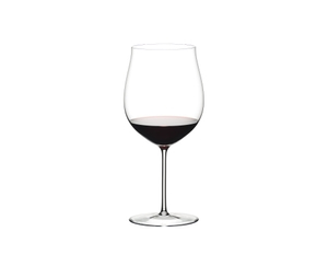 Red wine is being poured from a RIEDEL Amadeo Decanter into a RIEDEL Sommeliers Burgundy Grand Cru glass.