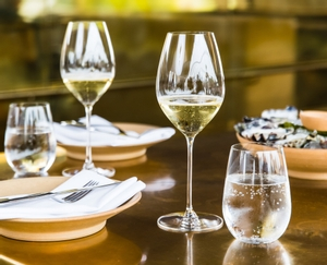 Two RIEDEL Veritas Champagne Wine Glasses and two O Wine Tumbler Riesling Sauvignon Blanc glasses on a golden table.