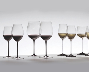 Various glasses of the RIEDEL Sommeliers Black Tie range filled with red and white wine on a grey ground.