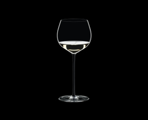 RIEDEL Fatto A Mano Oaked Chardonnay Black filled with a drink on a black background