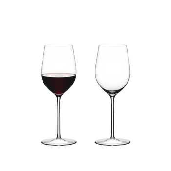Two RIEDEL Sommeliers Mature Bordeaux/Chablis/Chardonnay glasses stand side by side. The glass on the left side is filled with red wine, the other one is empty.