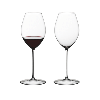 Two RIEDEL Superleggero Hermitage/Syrah glasses side by side. The one on the left is filled with red wine, the other one is empty.