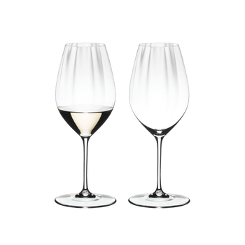 Two RIEDEL Performance Riesling glasses side by side. The glass on the left side is filled with white wine, the other one is empty.