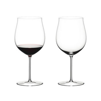 Two RIEDEL Sommeliers Burgundy Grand Cru glasses on white background. The glass on the left side is filled with red wine, the one on the right side is empty.