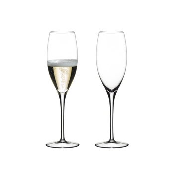 Two RIEDEL Sommeliers Vintage Champagne Glasses standing side by side. The glass on the left side is filled with Champagne, the other one is empty.