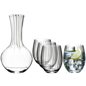 An unfilled RIEDEL Performance Decanter, a group of three unfilled Optical O Longdrink glasses and an Optical O Longdrink glass filled with a decorated Gin Tonic stand side by side.