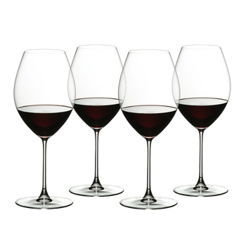 Four red wine filled RIEDEL Veritas Old World Syrah glasses stand slightly offset next to each other