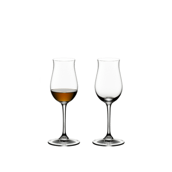 Two RIEDEL Vinum Cognac Hennessy glasses stand side by side. The glass on the left side is filled with Cognac, the other glass is empty.