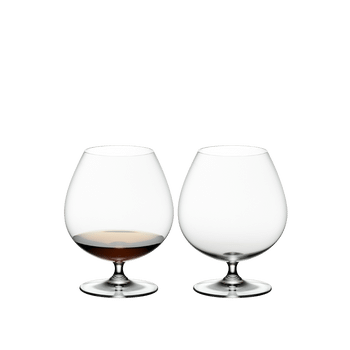 2 RIEDEL Vinum Brandy glasses standing side by side. One is filled with Brandy, the other glass is empty.