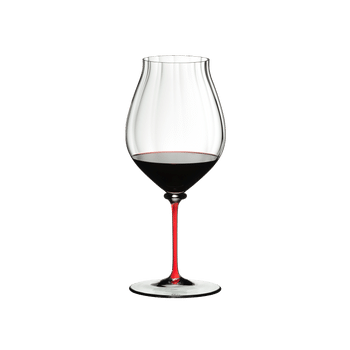 A RIEDEL Fatto A Mano Performance Pinot Noir glass with red stem filled with red wine.
