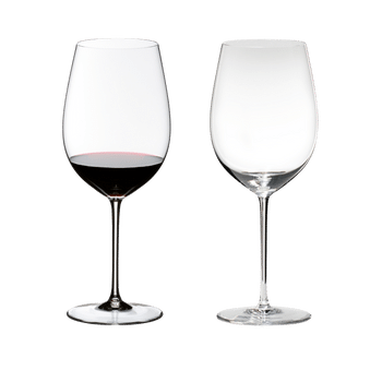 Two RIEDEL Sommeliers Bordeaux Grand Cru glasses on white background. The one on the left side is filled with red wine, the other one is empty.